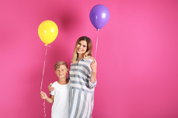 Mother and son with balloons on color background
