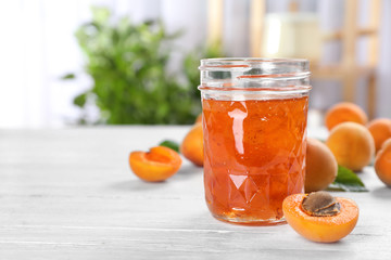 Jar with tasty apricot jam on table