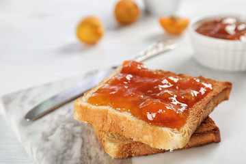 Bread with tasty apricot jam on board