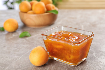 Bowl with tasty apricot jam on table