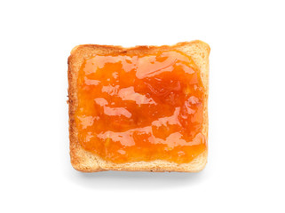 Bread with tasty apricot jam on white background, top view
