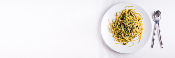 Top view of Oyster spaghetti served in white plate on white tablecloth. With copy space.
