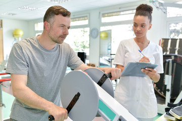 male patient with female physio therapist working out arms