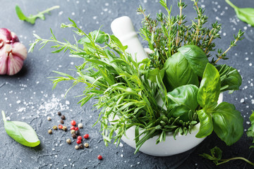 Photo Blinds Condiments Fresh green garden herbs in mortar bowl and spices on black stone table. Thyme, rosemary, basil, and tarragon for cooking.