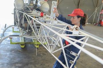 woman checking flying machine in hangar