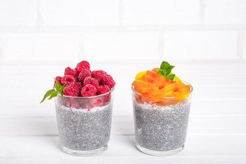 Healthy eating and dieting concept. Chia pudding with fresh berries and green leaves for breakfast on a light kitchen table. Two glasses, peach or apricot and raspberry.