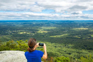 Woman takes a snpashot of the Hudson Valley farm land from Gertrude's Nose hiking trail, in Upstate New York