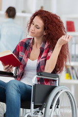 happy disabled woman sitting on wheelchair reading