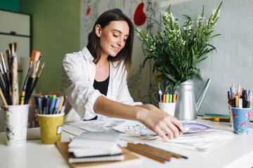 Smiling painter sitting at the desk with pictures happily drawing while spending time at home