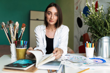 Pretty girl sitting at the desk with paintings dreamily looking in camera while thumbing a book at home