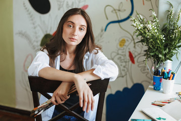Pensive girl in white shirt on chair thoughtfully looking in camera while holding paint brushes in hand with big painting on background at home