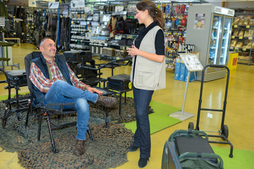 Man sat in chair in outdoor pursuits store