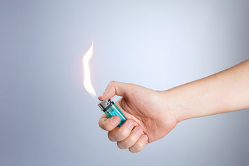 Hand burning a lighter on white background