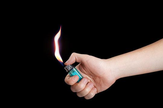 Hand burning a lighter on black background