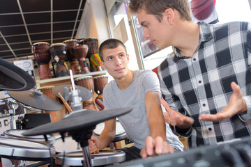 2 teens looking at drums in music store