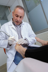 podiatrist cleaning womans feet