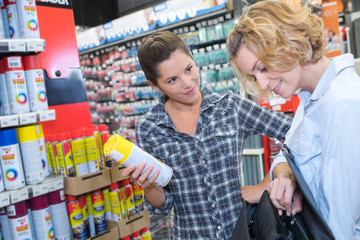 Shop assistant holding can of spray paint