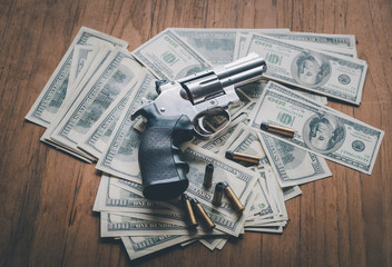 Gun with ammunition on the money dollars american background with concept business.