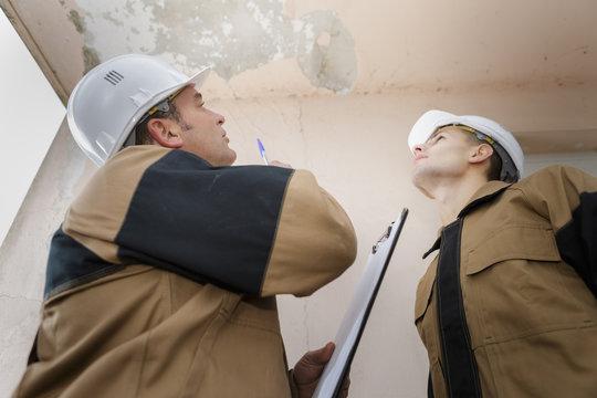 plumber looking at a ceiling leak