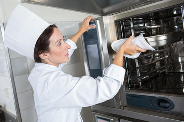 female chef putting something in industrial oven
