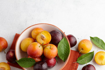 Fresh colorful plums with leaves in fruit bowl on white stone background, seasonal food