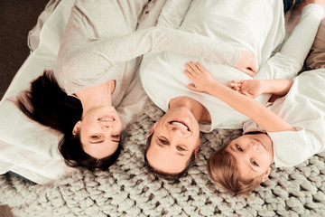 United family. Joyful delighted family lying together while smiling to you