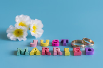 Multicolored inscription just married on a blue background. flowers