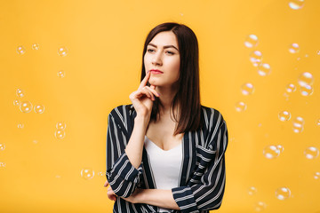 Woman and soap bubble around, yellow background
