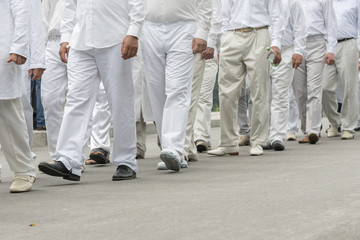 a group of people in white clothes. men in white stags are walking down the street.
