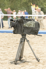 Television camera on the river beach. Lonely camcorder on a tripod. Vertical photo