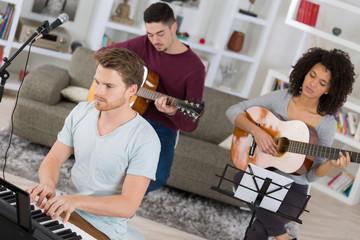 multiracial music band rehearsing at home