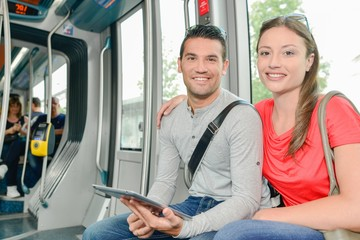 Couple on public transport holding tablet
