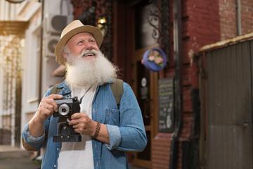 Happy smiling elder tourist glancing up