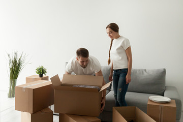 Millennial couple moving in to new flat, husband carrying cardboard boxes with personal belongings, happy young spouses settling relocating to first purchased or rented house. Living together concept