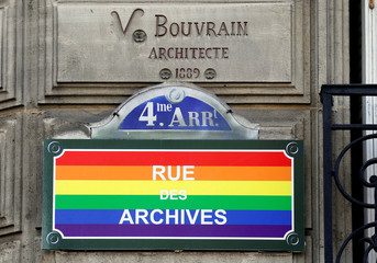 A road sign, painted as a rainbow flag, is pictured in the street near the Gay Games village at the Hotel de Ville city hall in Paris