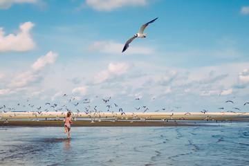 Girl running towards birds at the beach