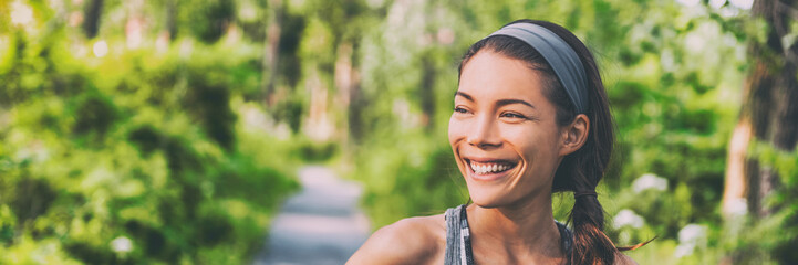 Obraz Happy young Asian woman outdoor walking in park smiling living an active and healthy lifestyle. Panoramic banner background. - fototapety do salonu