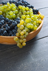 grapes on wooden bowl, black wood table background