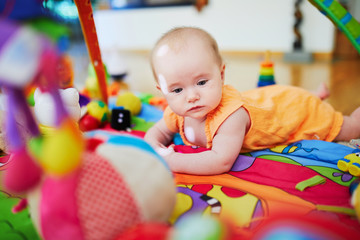 Baby girl with many colorful toys