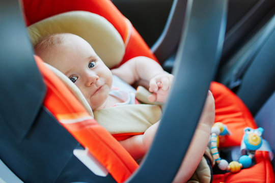 Adorable baby girl in modern car seat