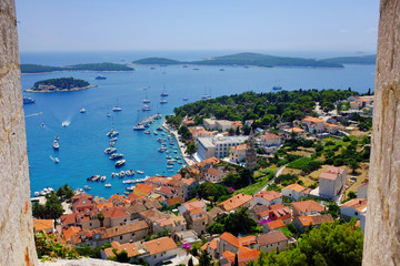 Hvar town harbor from the Spanish Fortress framed by a stone window
