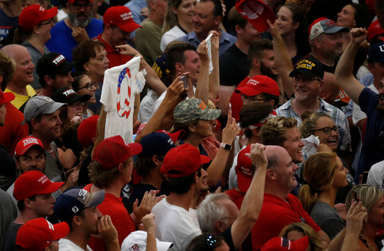 People cheer and hold up a QAnon shirt in the crowd as U.S. President Donald Trump holds a Make America Great Again rally in Olentangy Orange High School in Lewis Center, Ohio