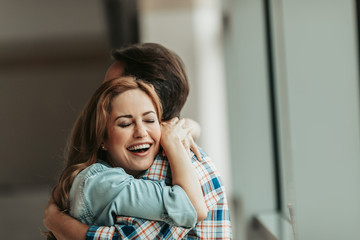 Laughing lady with attractive smile embracing man. Satisfied lovers concept