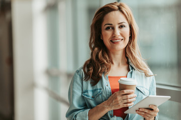 Portrait of happy girl tasting mug of hot liquid while typing in electronic tablet. Glad lady using appliance during rest concept