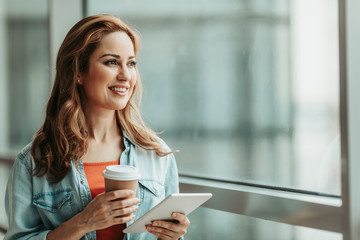 Portrait of smiling female drinking cup of coffee while holding digital device in hand. She looking at window