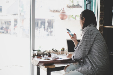 Mobile phone in woman's hands texting message, sitting in cafe with cup of coffee