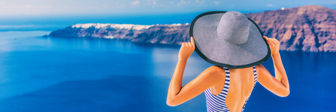 Luxury travel vacation lifestyle panoramic banner of woman sun tanning with hat in Santorini, Greece. Summer holiday destination panorama.