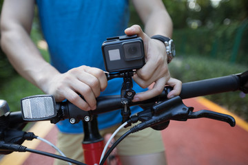 Cyclist mounting the action camera on mountain bike