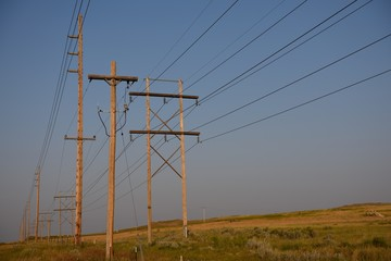 Rows of utility poles and overhead power supply wires at sunset in rural Wyoming / USA.