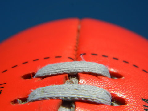 Close up of an Australian rules football on a blue sky background